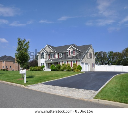 Suburban Two Story Double Garage Home with Fancy Blacktop Cobble Stone Driveway Mailbox on Curb Sunny Blue Sky Day - stock photo