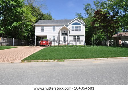 Suburban Two Story High Ranch Home Designer Driveway Parked Cars Sunny Blue Sky Day - stock photo