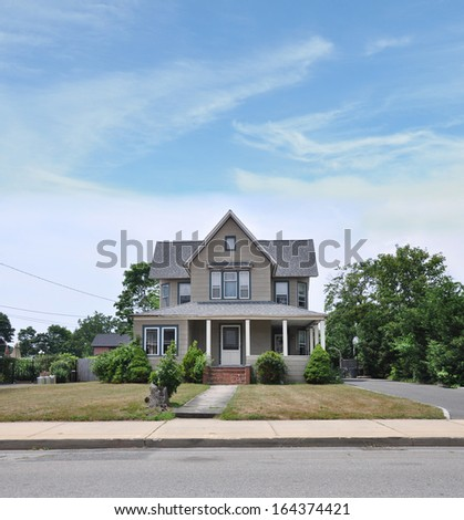 Suburban Victorian Style Home Exterior Front Yard Dry Grass Blue Sky Clouds Residential Neighborhood USA - stock photo