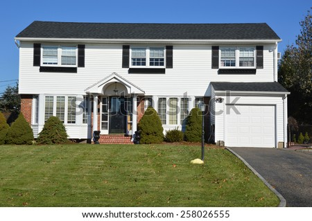 Suburban White and Black McMansion home sunny residential neighborhood clear blue sky day USA - stock photo