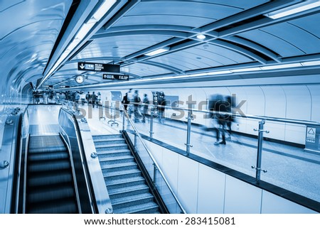 subway passage with commuters motion blur in guangzhou - stock photo