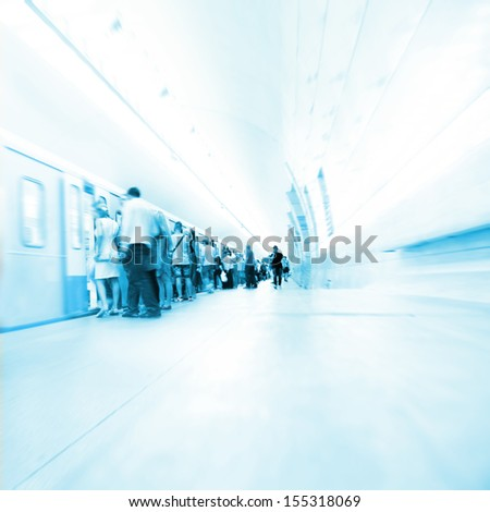 Subway train and passengers in motion blur.