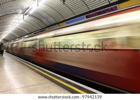 Subway train in motion arriving at a   underground train station. - stock photo