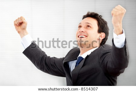 succesful business man in an office with his arms up