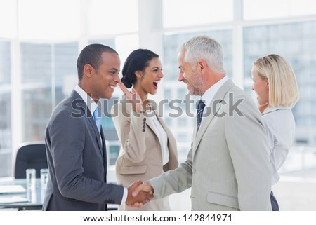 Succesful business team shaking hands and high fiving in the office - stock photo