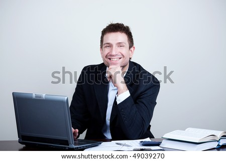 Succesful businessman sitting with laptop