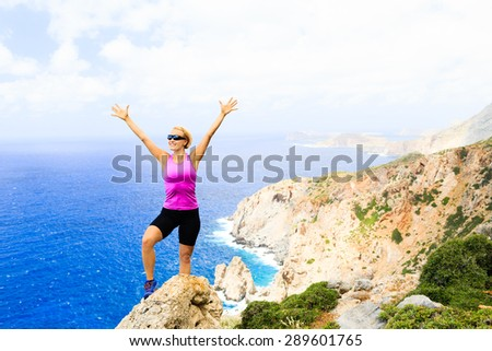 Success achievement climbing or hiking accomplishment concept, woman trail runner celebrating with arms up raised outstretched hiking, climbing or cross country running healthy lifestyle - stock photo