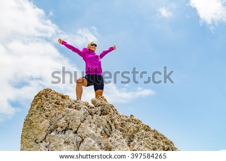 Success achievement running or climbing accomplishment business concept, woman celebrating with arms up raised. Hands outstretched on hiking trip. Trail Running concept in inspirational landscape. - stock photo
