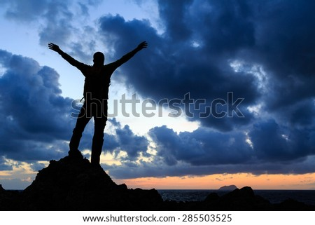 Success achievement silhouette, accomplish hiking accomplishment business concept with man celebrating with arms up raised outstretched faith worship outdoors - stock photo