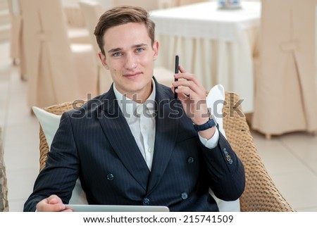 Success and persistence. Confident and successful businessman sitting in office and holding a cell phone looking at the camera and smiling while drinking coffee - stock photo