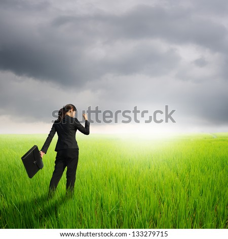 Success Business woman holding bag in green rice field and raincloud
