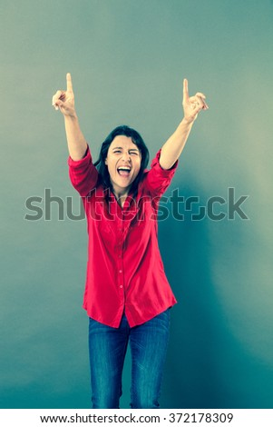 success concept - ecstatic 30s woman laughing with extrovert hand gesture to express euphoria or vitality,studio shot, blue effects