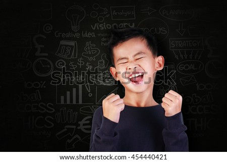 Success concept, portrait of happy young Asian boy showing enthusiastic winning gesture shout with joy of victory over blackboard with business doodle scheme drawn on it