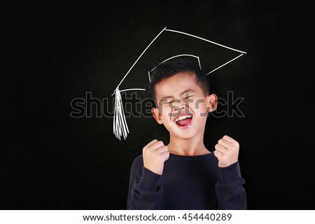 Success concept, portrait of happy young Asian student boy showing enthusiastic winning gesture, shout with joy of victory, over blackboard with graduation hat drawn above his head - stock photo