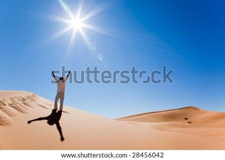 Success concept: rear view of a adult white man standing on a sand dune and holding arms up. Erg Chebbi, Maroc - stock photo