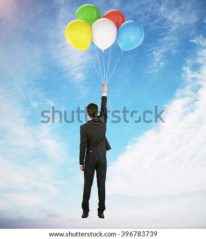 Success concept with businessman holding onto colorful balloons in blue skies