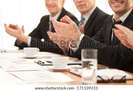 Success. Cropped image of people in formalwear sitting together at the table and applauding you - stock photo