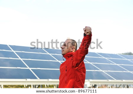 Success, engineer in solar panel fields opening arms up