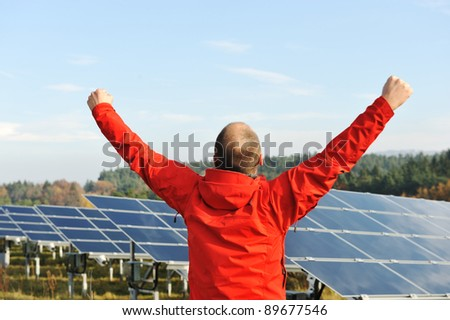 Success, engineer in solar panel fields with arms up - stock photo