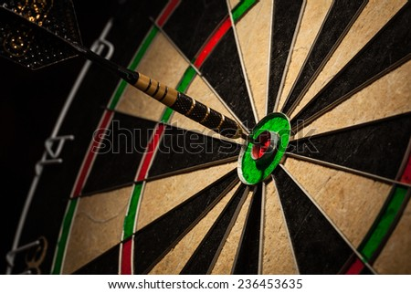 Success hitting target aim goal achievement concept background - dart in bull's eye close up