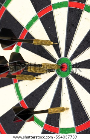 Success hitting target aim goal achievement concept background - darts in bull's eye close up