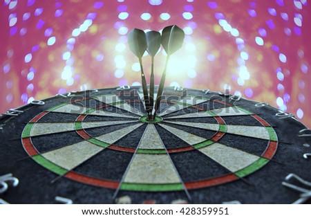 Success hitting target aim goal achievement concept background - three darts in bull's eye close up - stock photo