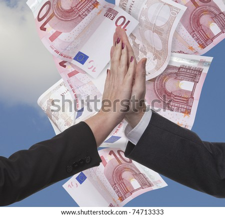 Success in Europe. A businessman and woman partnership doing a high five over a background of Euro banknotes - stock photo