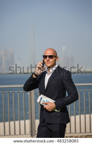 Success manager in formal suit staying in waterfront. Businessman holding newspaper and call.