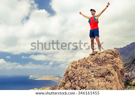 Success motivation man running or hiking, achievement successful and happiness concept, man celebrating with arms up raised outstretched climbing  or trail running outdoors, healthy lifestyle - stock photo