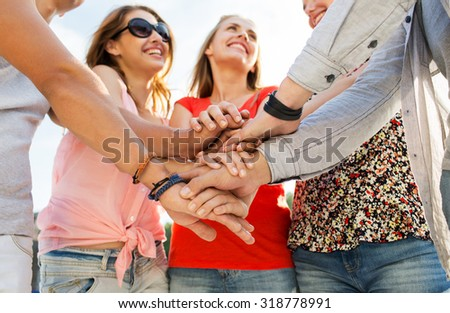 success, people, teamwork and gesture concept - close up of happy  friends  with hands on top of each other outdoors - stock photo