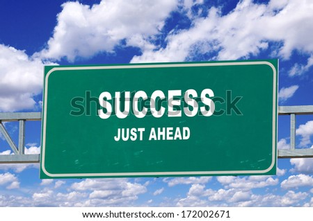 Success sign on the green board with clouds in background