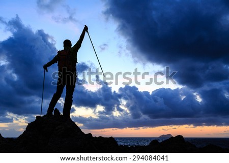 Success silhouette backpacker on top, man looking at inspirational ocean and island, relaxing or camping in mountains on mountain peak. Motivation for fitness and healthy lifestyle outdoors in nature. - stock photo
