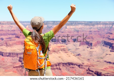 Success winner person happy hiker in Grand Canyon. Woman cheering with arms raised up in winning gesture enjoying the beautiful landscape. Hiking girl wearing backpack during summer in, Arizona, USA. - stock photo