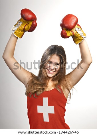 Success woman celebrating  for her succes with the flag of switzerland on her shirt on grey - stock photo