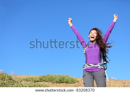 success woman happy outside on adventure cheering with arms in the air screaming cheerful with winning attitude while hiking. Beautiful young mixed race Caucasian Asian female hiker. - stock photo