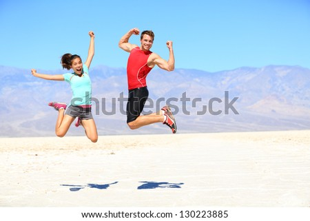 Success. Young runners jumping excited celebrating cheering happy and energetic in desert landscape. Young joyful fitness interracial fit fitness sport couple, Asian woman, Caucasian man outdoors. - stock photo
