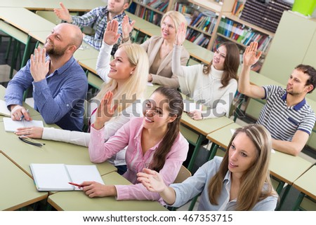 Successful adult students sitting in classroom with hands up. Selective focus