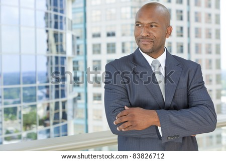 Successful African American businessman or man arms folded in a suit in a modern city
