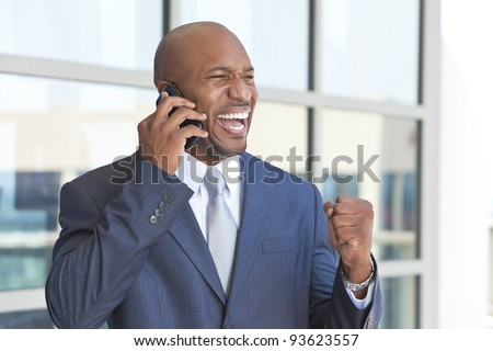 Successful African American businessman or man in a suit in a modern city talking on his cell phone celebrating success - stock photo