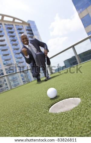 Successful African American businessman or man in a suit playing golf on putting green on office building roof, focus in this image is on the ball, other images in portfolio the focus is on the man. - stock photo