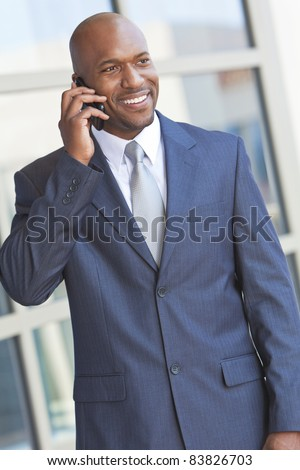 Successful African American businessman or man talking on his cell phone in a modern city - stock photo
