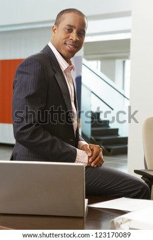 Successful African American businessman sitting on top of his desk alongside a laptop