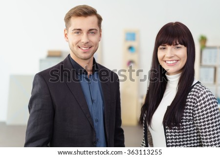 Successful ambitious young business team with an attractive friendly man and woman posing together in the office - stock photo