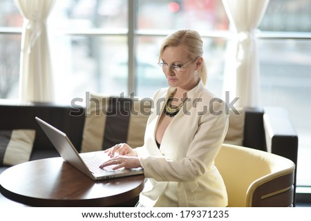 Successful and attractive middle aged businesswoman working on the laptop computer in the hotel lounge - stock photo