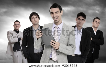 Successful and confident business leader and holding a tablet computer in front of his team - stock photo