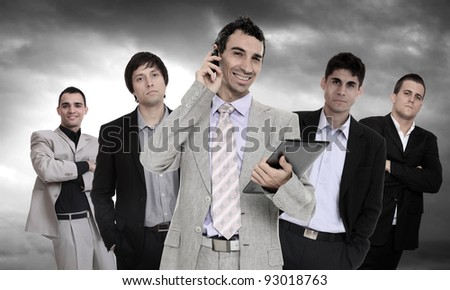 Successful and confident business leader talking on the phone and holding a tablet computer in front of his team - stock photo