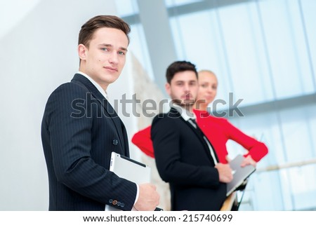 Successful and confident businessman. Young businessman standing on the steps and keeps the tablet while his colleagues talk and resolve things with each other - stock photo