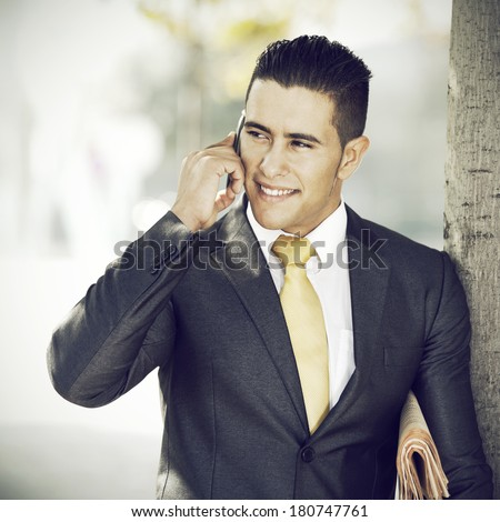 Successful and handsome businessman talking at his cellphone next to a tree - stock photo