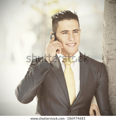 Successful and handsome businessman talking at his cellphone next to a tree