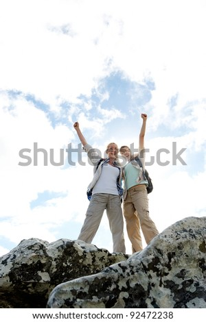 successful and happy hiking women on top of a rock - stock photo